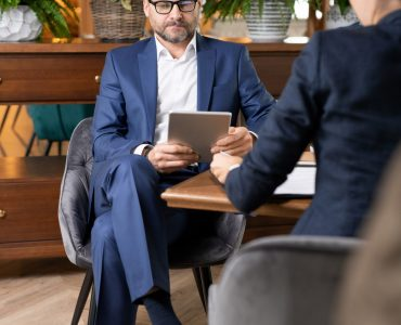 Busy employee in elegant suit sitting by table in restaurant and scrolling in touchpad with his colleague working in front