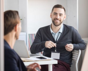 Portrait of cheerful bearded office worker talking to colleague at workplace